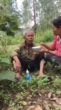 Người phụ nữ mang cơm lên núi bón cho cụ già đi lạc