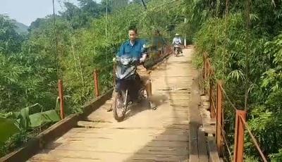 """Người dân """"liều mình"""" qua sông trên cây cầu treo cũ nát ở Hòa Bình"""