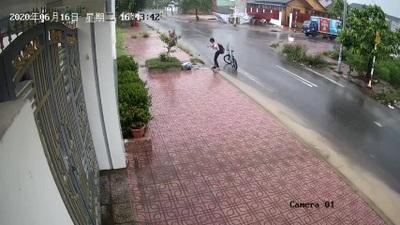 Cậu học sinh dừng xe nhặt rác khơi thông miệng cống trong cơn mưa to
