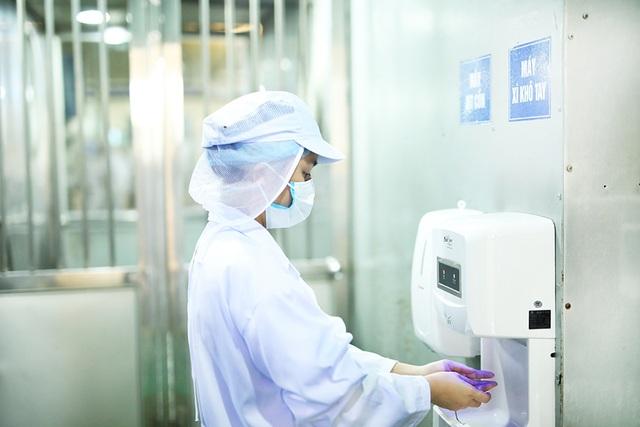 Công nhân phải mặc trang phục bảo hộ lao động, rửa sạch tay, xịt cồn và đeo găng tay trước khi bước vào xưởng.