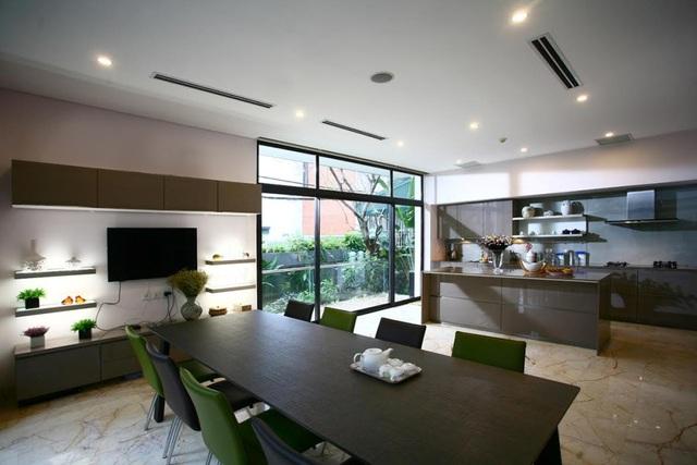 Phòng bếp được thiết kế hiện đại, tiện nghi. Chủ nhà khéo léo sử dụng nội thất mang sắc nâu trầm, tương phản với màu trắng của trần và tường. Hệ thống đèn cũng được lắp đặt khá tiết chế, tận dụng tối đa ánh sáng bên ngoài.