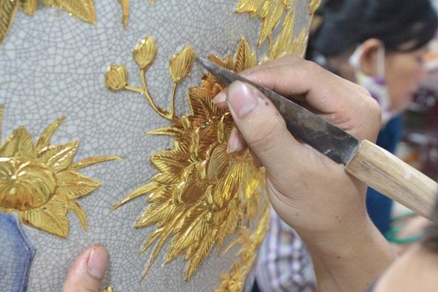 """Nói về công đoạn dát vàng, cô Lê Thị Hậu – nghệ nhân dát vàng làng Kiêu Kỵ cho biết: """"Vàng vốn rất mỏng nên chúng tôi phải kì công dát từng chút một. Trước hết, phải đợi khô sơn lót rồi mới có thể bắt tay vào làm. Tính ra trung bình, 1 bộ gốm dát vàng cần sử dụng khoảng hơn 3 cây vàng mới hoàn thiện""""."""