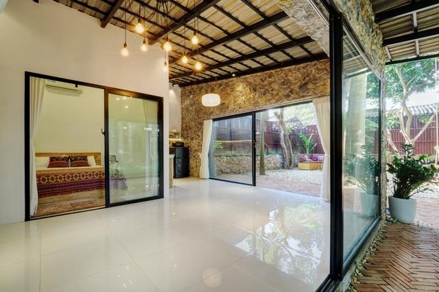 Để tạo sự thông thoáng cho không gian, KTS đã sử dụng chất liệu kính khá nhiều cho cửa ra vào, cửa sổ hay cửa ngăn cách các phòng. Đá và kính vốn là 2 vật liệu đối lập, nhưng khi đặt cạnh nhau lại có sự hòa hợp đến kỳ lạ.