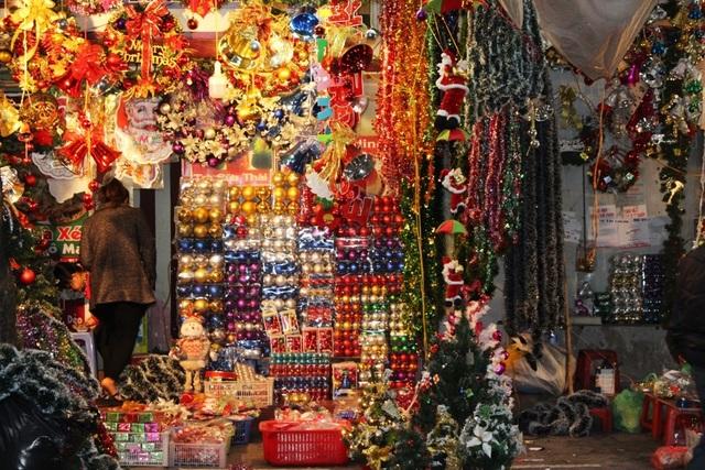 Càng gần đến Giáng sinh, lượng người đổ về phố Hàng Mã càng lớn. Cả một dãy phố, cửa hàng nào cũng bày bán các món hàng trang trí Noel như vòng nguyệt quế, cây thông, chuông, đèn led, quả châu cùng hàng trăm món phụ kiện khiến con đường trở nên vô cùng lấp lánh.