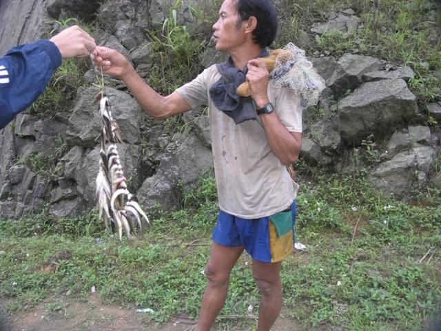 Một người dân Sa Pa mời khách du lịch mua cá suối đánh bằng lưới