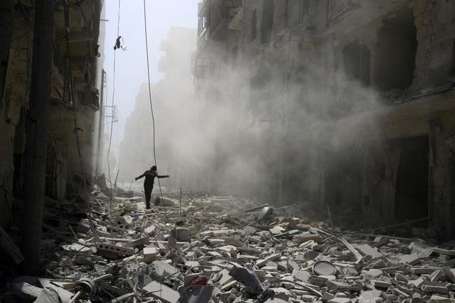 Một người đàn ông đi qua các tòa nhà bị phá hủy sau một cuộc không kích tại khu vực al-Qaterji của Aleppo, Syria. (Ảnh: Reuters)