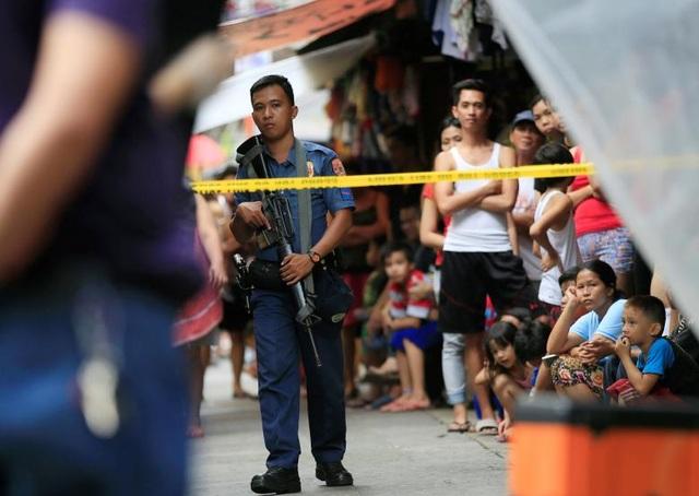 Một cảnh sát Philippines bảo vệ hiện trường nơi hai kẻ buôn lậu ma túy bất hợp pháp bị bắn chết tại thủ đô Manila (Ảnh: Reuters)