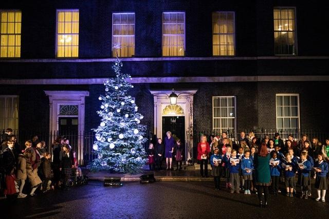Thủ tướng Anh Theresa May và các học sinh cùng thắp sáng cây thông Giáng sinh bên ngoài Phủ thủ tướng Anh ở London. (Ảnh: Getty)