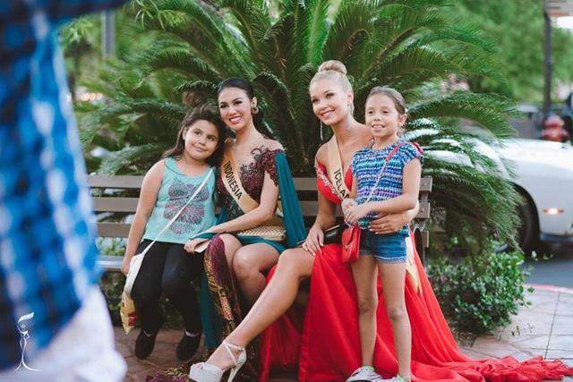 Hoa hậu Indonesia và Ai-len chụp ảnh cùng fan nhí trước sự kiện.