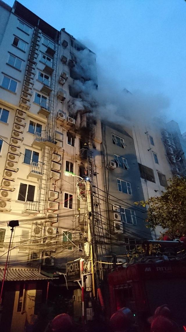 Trời tối dần, khói vẫn bốc ra khá mạnh trên các tầng trên của ngôi nhà 10 tầng.