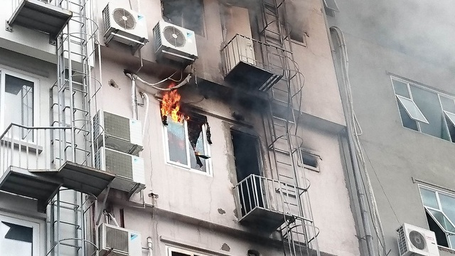 Phía sau ngôi nhà được cho là quán karaoke đã xảy ra cháy đầu tiên, khói và lửa vẫn bốc ra.
