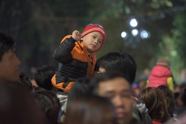 Một em bé phấn khích theo điệu nhạc của DJ khi ngồi trên vai bố ở khu vực tháp nước Bờ Hồ (Ảnh: Mạnh Thắng)
