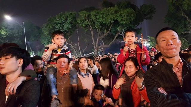 Những đứa trẻ trên vai cha mẹ, háo hức chờ đón thời khắc giao thừa. (Ảnh: Thế Kha)
