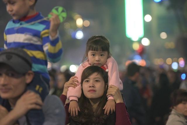 Một em nhỏ theo mẹ hòa vào dòng người đi đón xuân. (Ảnh: Mạnh Thắng)