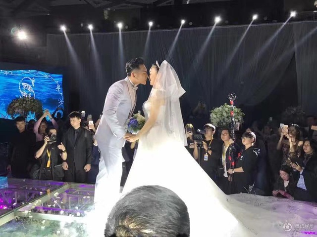 Chú rể dịu dàng hôn môi cô dâu trong tiệc cưới ấm cúng.