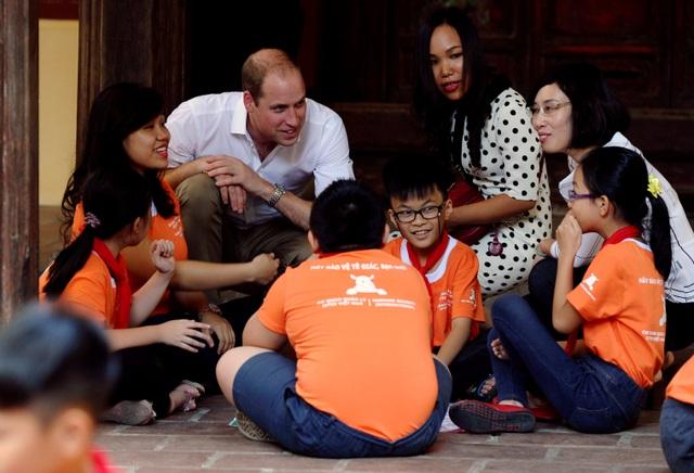 Hoàng tử William thích thú xem các học sinh chơi các trò chơi dân gian của Việt Nam. (Ảnh: Reuters)