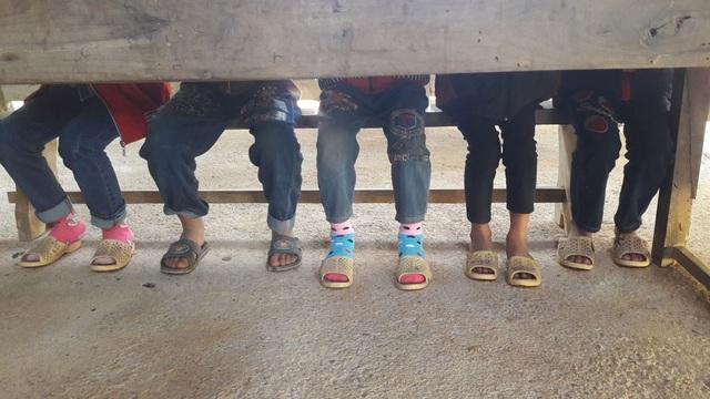 Trong 4 phòng học thì có 2 phòng được đổ xi măng, còn 2 phòng chỉ là nền đất. Các em học sinh đứa nào cũng giống nhau với dép lê, quần jeans sờn nát và úa màu