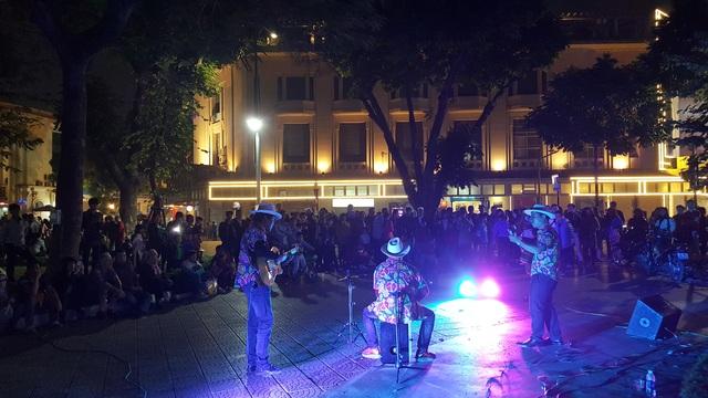 Một nhóm nhạc biểu diễn góc đường Đinh Tiên Hoàng-Hàng Khay thu hút rất đông người dân theo dõi. (Ảnh: Thế Kha)