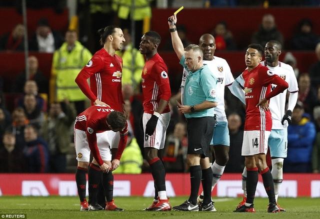 Pogba (giữa) nhận thẻ vàng từ trọng tài Moss