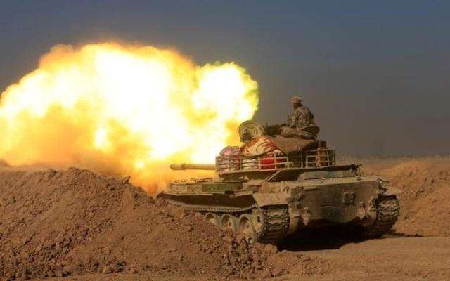 Các binh sĩ thuộc quân đội Iraq khai hỏa về phía các vị trí của nhóm phiến quân Nhà nước Hồi giáo (IS) phía nam Mosul, Iraq. (Anh: Reuters)