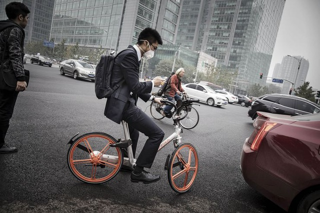 Một người đàn ông đang sử dụng xe đạp của công ty Beijing Mobike ở Bắc Kinh. Ảnh: Bloomberg