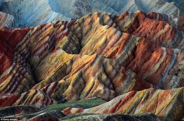 Tới thăm công viên địa chất Zhangye Danxia ở Cam Túc, nhiều du khách sẽ thích thú với những núi đá nhiều màu sắc và hình thù kỳ lạ. Đây là kết quả của hàng triệu năm tích tụ sa thạch đỏ và các trầm tích trở nên khô cằn, oxy hóa. Theo mưa gió thời gian xói mòn đã tạo hình cho núi đá, khiến chúng mang nhiều hình dạng khác nhau như thung lũng, thác nước hay cột đá.