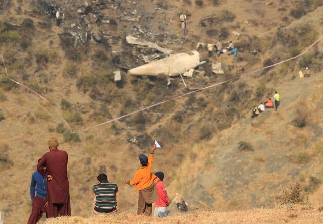 Một bé trai chơi máy bay giấy gần hiện trường vụ tai nạn máy bay thảm khốc làm gần 50 người chết tại làng Saddha Batolni gần Abbotabad, Pakistan. (Ảnh: Reuters)