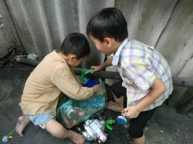 Hai anh em túm tụm quanh túi đồ chơi hỏng bị bỏ ngoài đường
