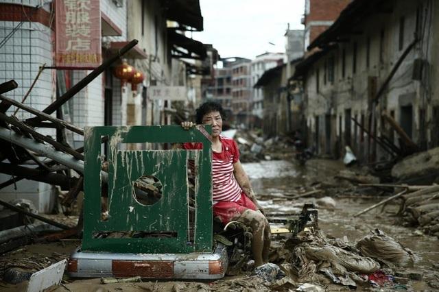 Một người phụ nữ buồn bã ngồi trên đống đổ nát sau khi cơn bão Nepartak quét qua tỉnh Phúc Kiến, Trung Quốc hồi tháng 7. (Ảnh: Reuters)
