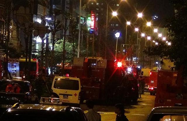 Xe cứu thương túc trực bên ngoài các ngôi nhà bị cháy
