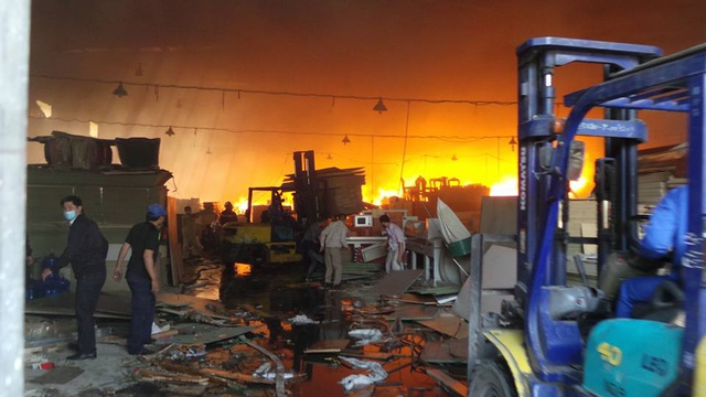Phía trong cháy lớn, phía ngoài các công nhân vẫn đang nỗ lực giải cứu hàng hóa.