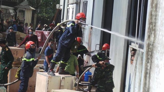 11h35, lực lượng chữa cháy phá tường, phun nước vào bên trong kho gỗ.