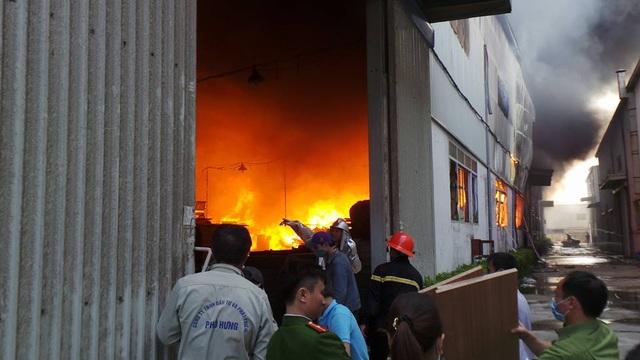 Lửa đỏ rực trong nhà xưởng. Các công nhân nỗ lực cứu tài sản.