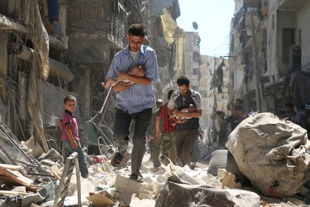 Những người đàn ông bế trên tay những đứa trẻ sơ sinh, chạy qua đống đổ nát sau cuộc không kích ở Aleppo, Syria hôm 11/9. (Ảnh: AFP)