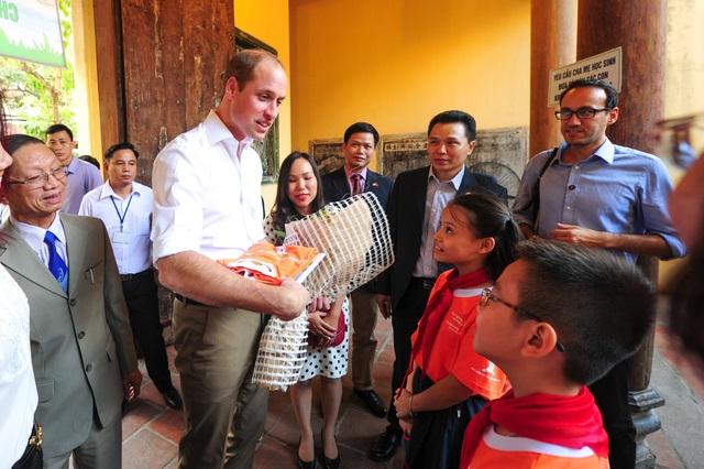 Hai học sinh thay mặt các bạn cùng trường tiểu học Hồng Hà tặng hoa và quà lưu niệm cho Hoàng tử William. (Ảnh: Đại sứ quán Anh tại Việt Nam)