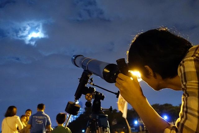 Nam thanh niên say sưa quan sát siêu trăng qua kính thiên văn.