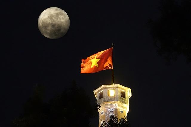 Trăng treo trên cột cờ Hà Nội lúc 20h. Siêu trăng là hiện tượng trăng ở vị trí rất gần trái đất so với cả quỹ đạo, vào đúng thời điểm trăng tròn.