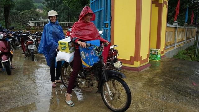 Những người dân ở xã Xuân Trạch đội mưa mang quà về nhà trong niềm hạnh phúc