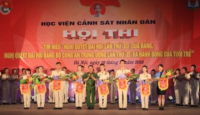 Đại diện các đội thi nhận hoa và cờ lưu niệm từ Phó Giám đốc Học viện - Thiếu tướng, PGS.TS Đặng Xuân Khang.