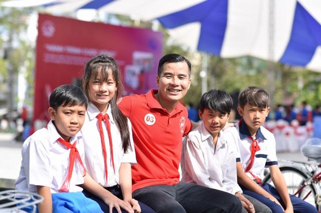 Phó Tổng Giám đốc Tài chính AIA Việt Nam, ông Lý Nhơn chung vui cùng các cháu học sinh được nhận xe đạp trong Hành trình Cuộc sống tại Cần Thơ