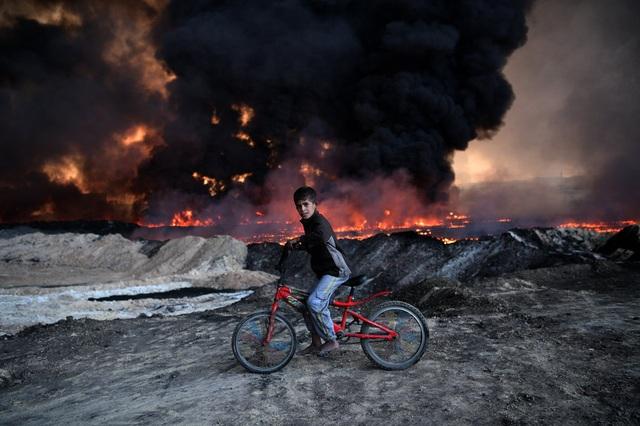 Một cậu bé đạp xe qua một mỏ dầu đang bốc cháy ngùn ngụt do các tay súng của tổ chức Nhà nước Hồi giáo tự xưng (IS) phóng hỏa trước khi rút lui khỏi thành phố Mosul, Iraq ngày 21/10. (Ảnh: Getty)