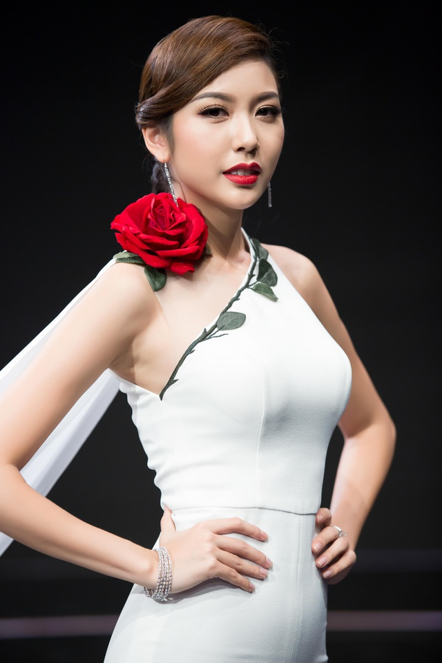 Tổng thể trang phục đơn màu nhưng không nhàm chán bởi bông hoa hồng đỏ và layout make up sang trọng, cổ điển. Với kỹ thuật make-up tạo điểm nhấn vào bờ môi đỏ nổi bật và đôi mắt vẽ eyeliner đen đậm