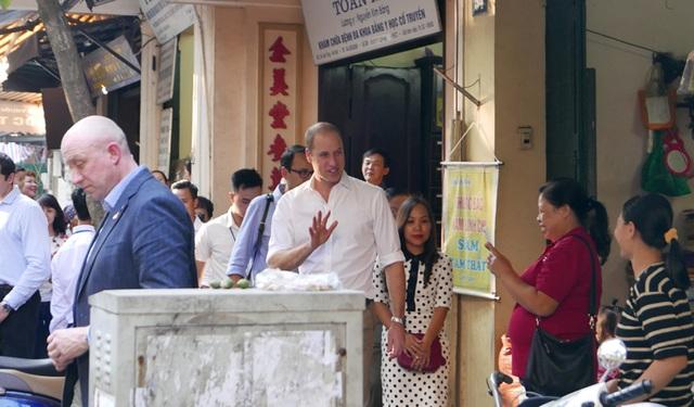 Công tước xứ Cambridge vẫy tay chào người dân khi bước ra từ cửa hàng thuốc bắc.