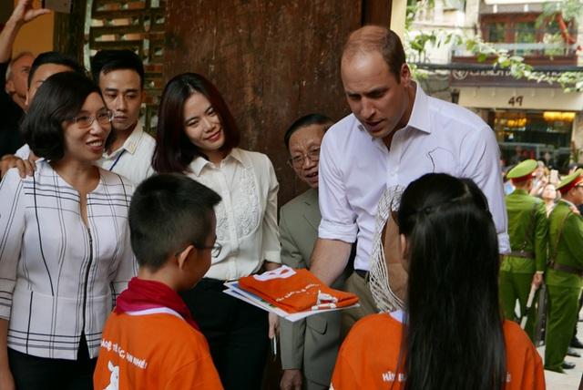 Một học sinh thay mặt các bạn cùng trường tặng quà cho Hoàng tử William.