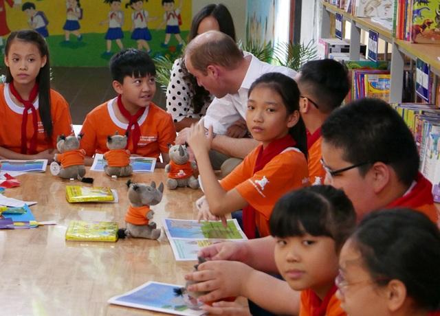 """Hoàng tử đã vào thăm thư viện của trường và cùng các học sinh đọc cuốn sách """"Tớ là chú Tê giác nhỏ bé""""."""