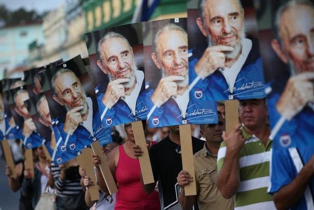 Người dân mang theo di ảnh khi đón đoàn xe chở tro cốt của cố lãnh tụ Fidel đi qua. (Ảnh: Reuters)