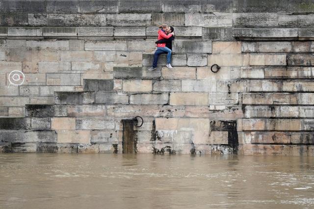 Một cặp đôi bày tỏ tình cảm trong những ngày nước lũ dâng cao ở thủ đô Paris, Pháp hồi đầu tháng 6. Bên dưới chân họ là dòng sông Seine nổi tiếng của Pháp. (Ảnh: Reuters)