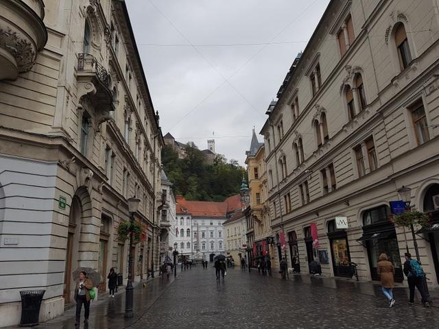 Tuyến phố chính của Thủ đô Ljubljana ngày chủ nhật có mưa. Phía sau là ngôi nhà thờ cổ được cho là bằng đá cổ nhất ở đây