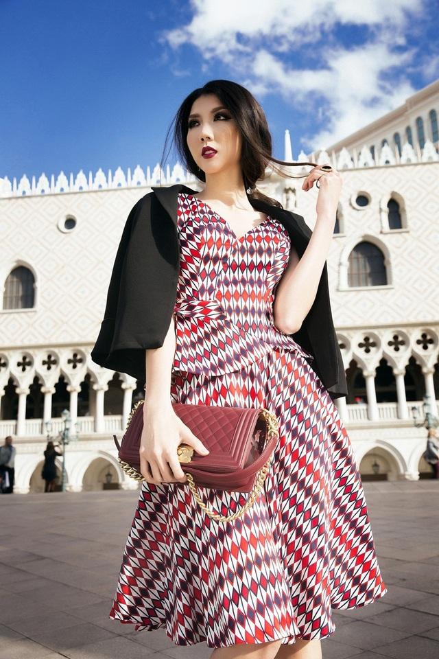 Sự bắt mắt của bộ trang phục còn phải kể đến kiểu áo khoác gam đen khá ăn ý, ton sur ton với tông đỏ của chiếc váy.