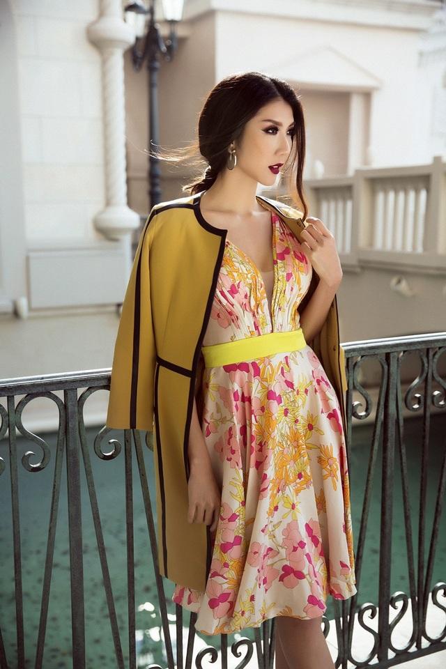 Cô kết hợp cùng áo khoác dáng dài tông vàng đất nhằm trung hòa gam màu nóng của bộ váy.